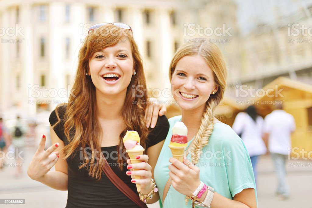 Young women together eating icecream stock photo