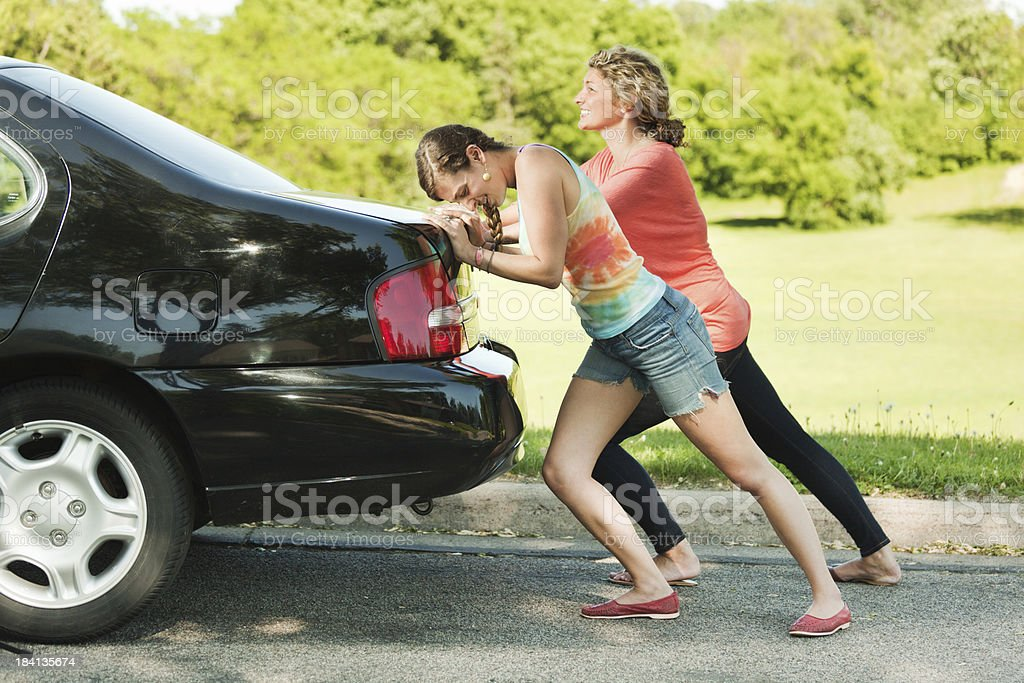 Young Women Travelers with Road Problem Pushing Their Car Forward stock photo