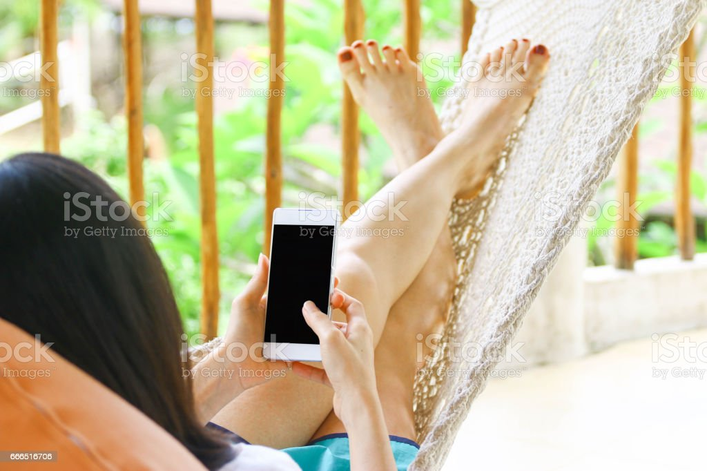 young women using mobile smart phone while relaxing in a cradle stock photo