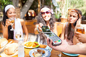 Young women using smart phone for contactless payment in restaurant