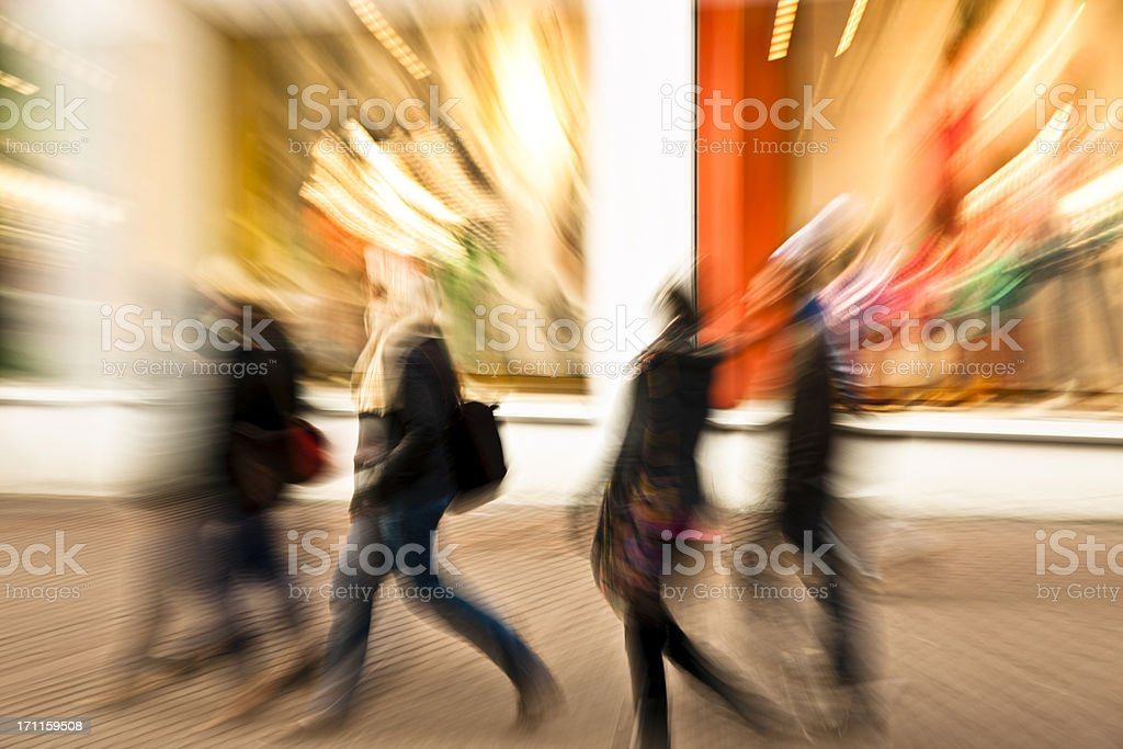 Young Women Walking Down Shopping Street, Blurred Motion royalty-free stock photo