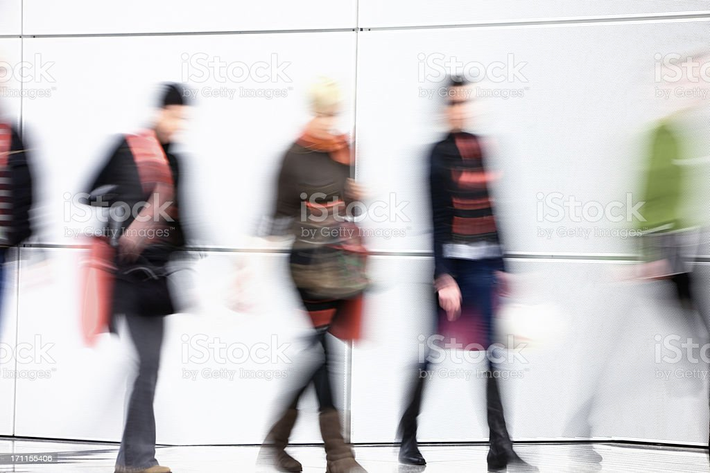 Young Women Walking in Hallway, Carrying Shopping Bags, Blurred Motion royalty-free stock photo