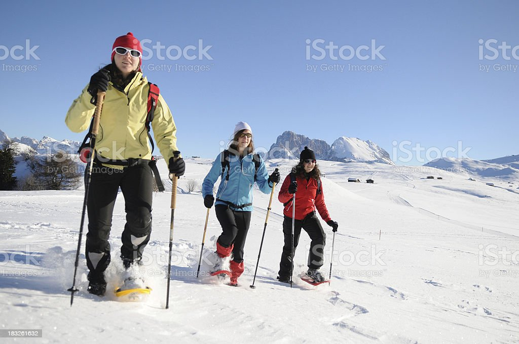 young women walking with snowshoes royalty-free stock photo