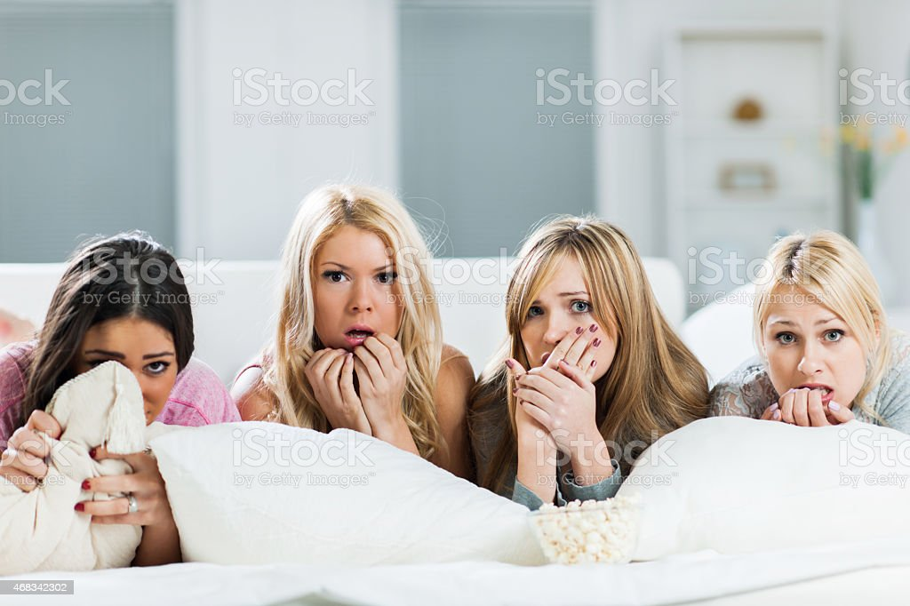 Young women watching a horror movie at home. stock photo