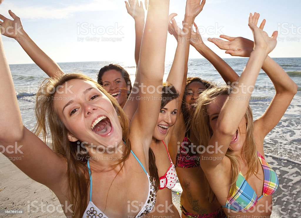 Young women with arms raised on the beach royalty-free stock photo