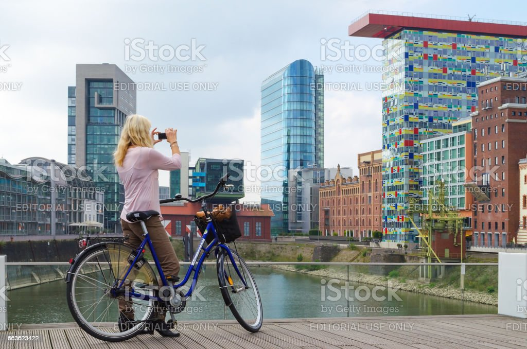 A young women with citybike takes photo of buildings in media harbor stock photo