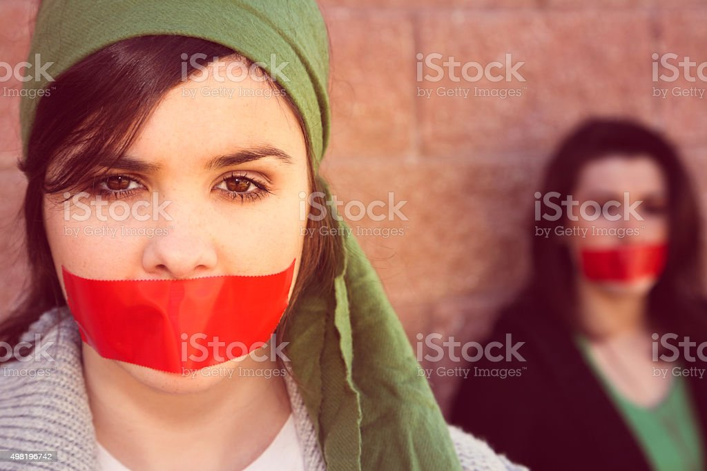 Young women with red tape over mouths in protest stock photo