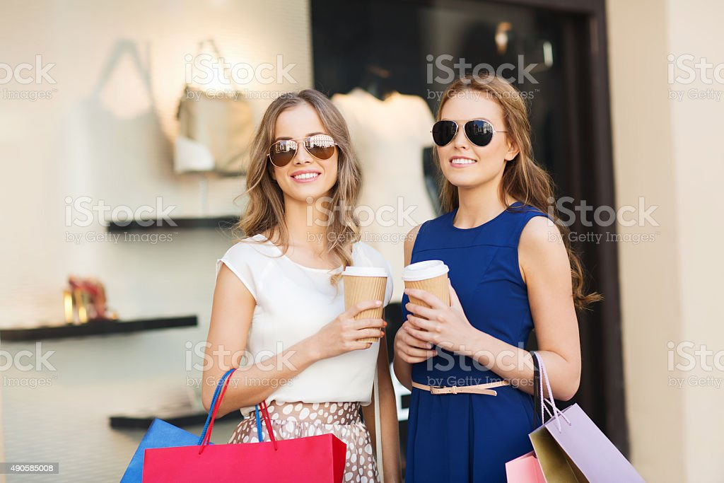 young women with shopping bags and coffee at shop stock photo