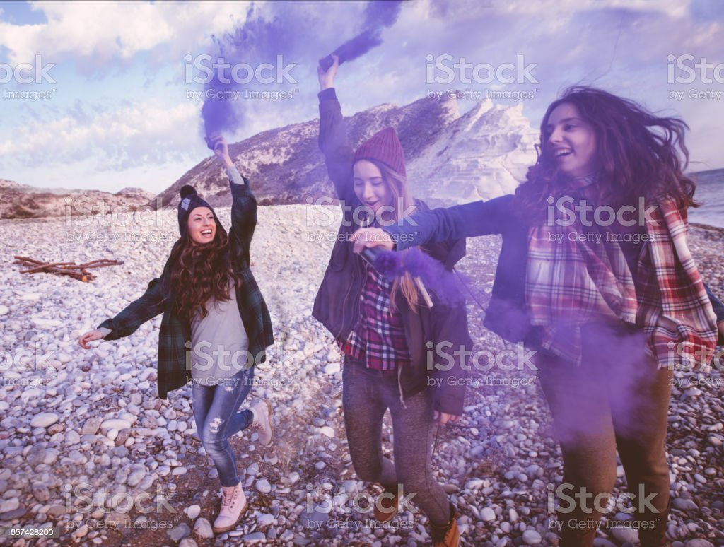 Young women with smoke bombs at the beach stock photo
