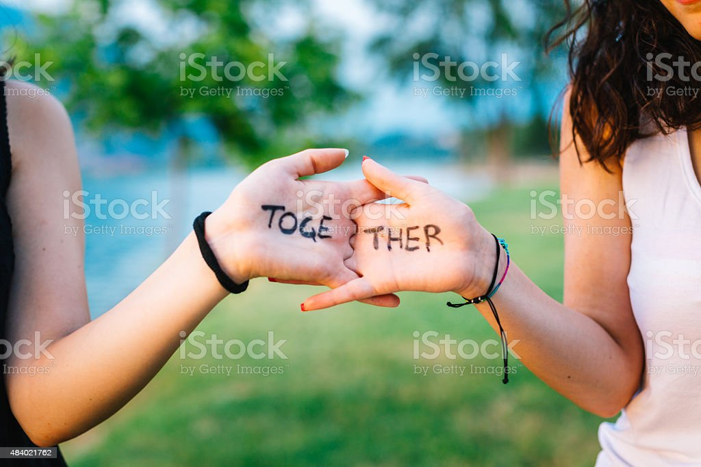 Young women with the word together on hands. stock photo