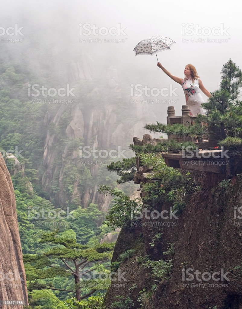 Young women with umbrella on the top of mountain royalty-free stock photo