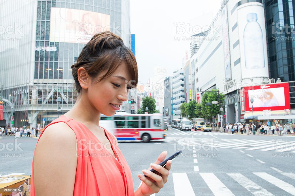 young womon checking a smartphone at Shibuya crossing stock photo
