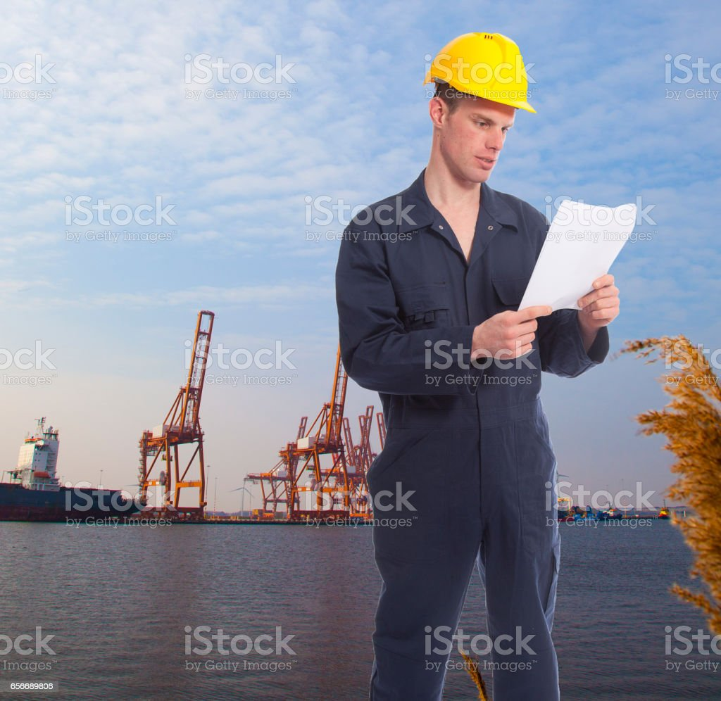 Young worker at harbor with cranes on background stock photo