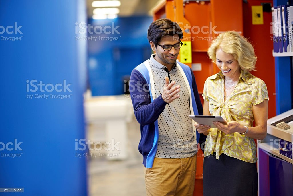 Young technician having conversation with female manager using...