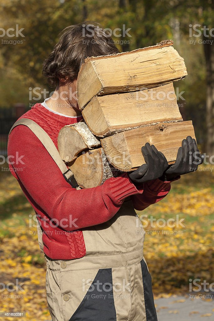 Young worker holding a stack of firewood stock photo