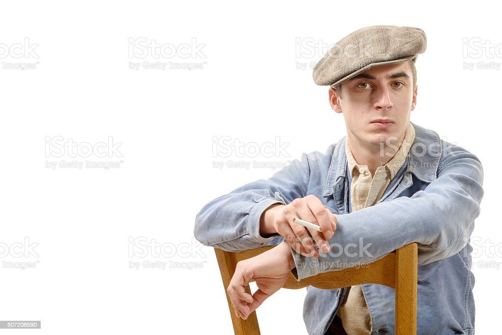 young  worker in vintage clothing, sitting on a chair stock photo