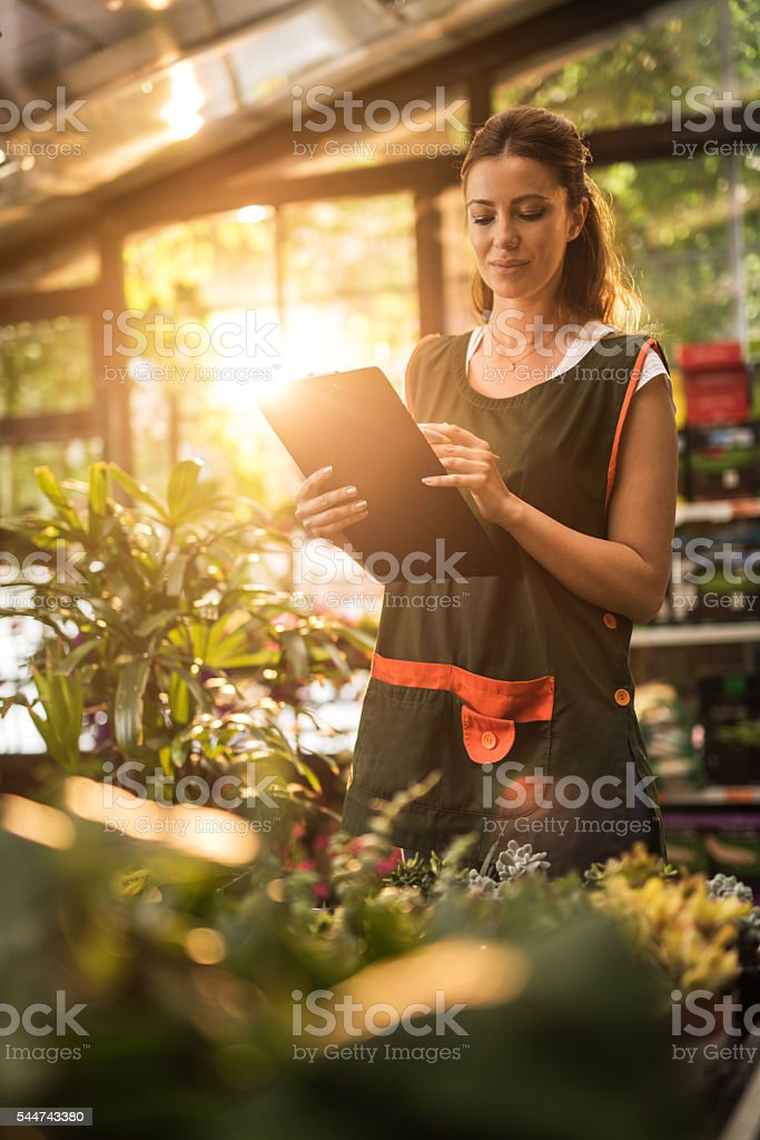 Young worker taking notes in a garden center. stock photo