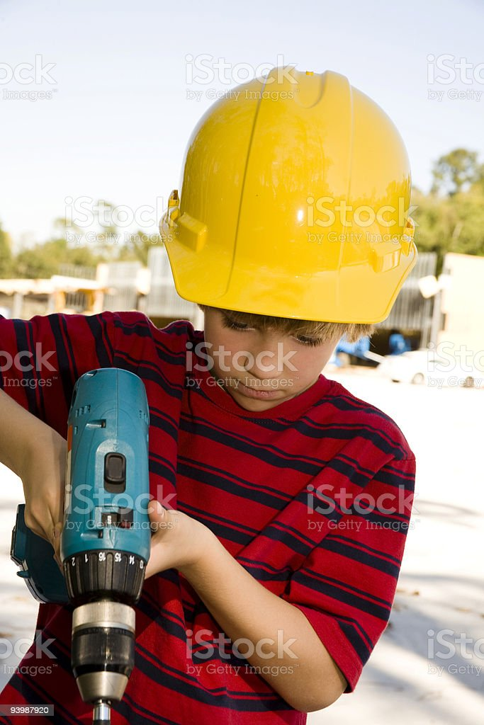 Young worker with cordless drill wearing hardhat at jobsite royalty-free stock photo
