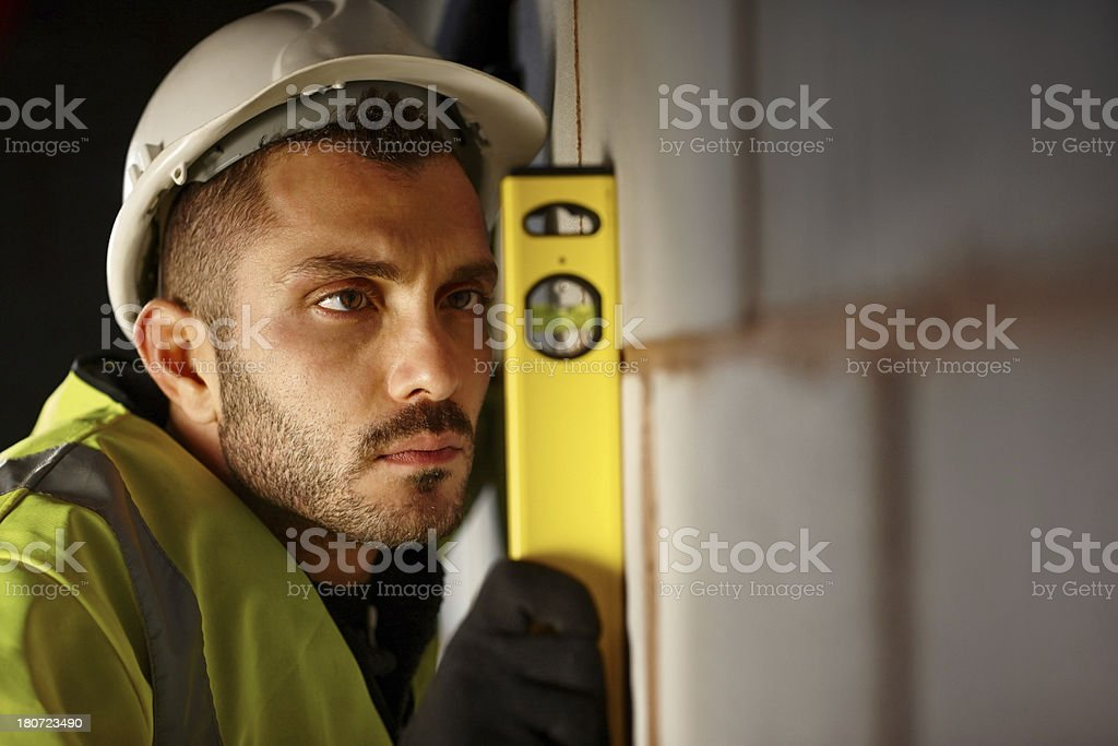 Young worker with hard hat checking level royalty-free stock photo