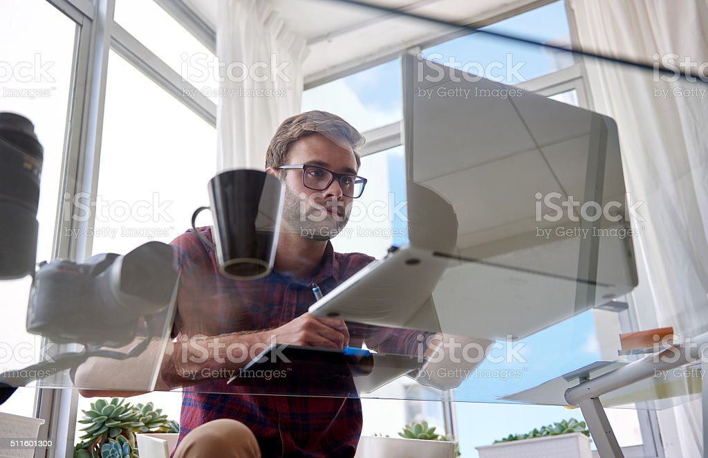 Young working man shot from under a glass table stock photo