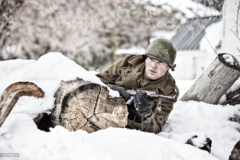 Young WWII GI Rolling for Shelter Behind Snow Covered Log stock photo