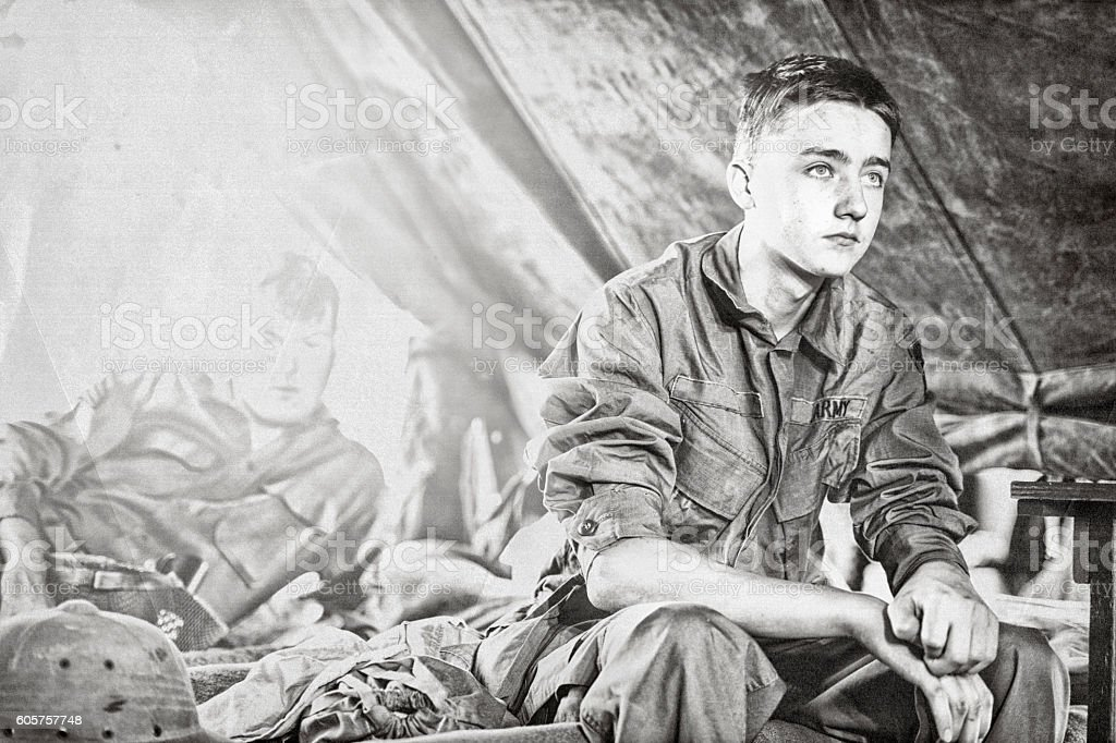 Young WWII Infantryman Sitting On A Cot In His Tent stock photo