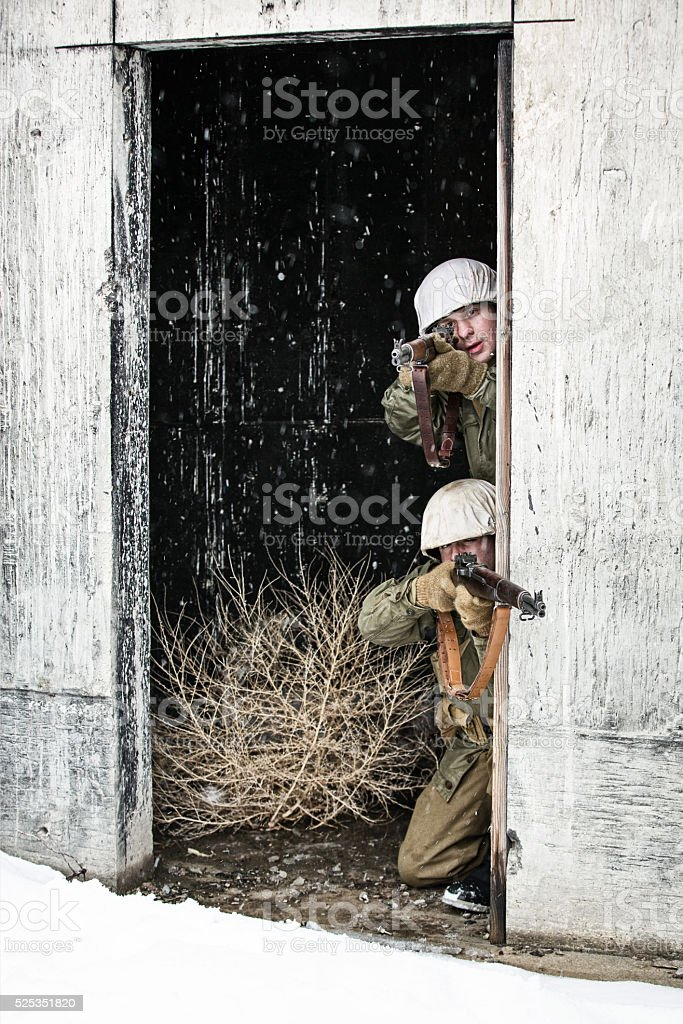 Young WWII US Infantry Soldiers Shooting From A Bunker stock photo
