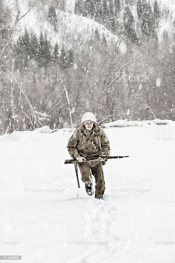 Young WWII US Soldier Crossing An Open Snowy Field stock photo