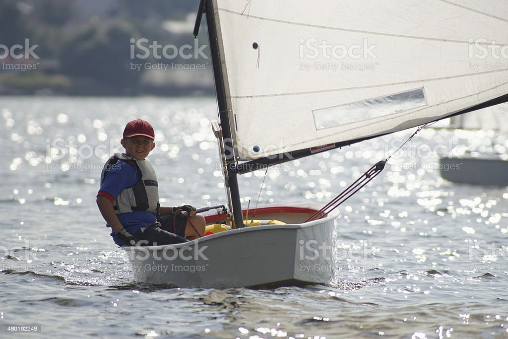 Young yachtsman manages dinghies Optimist. stock photo