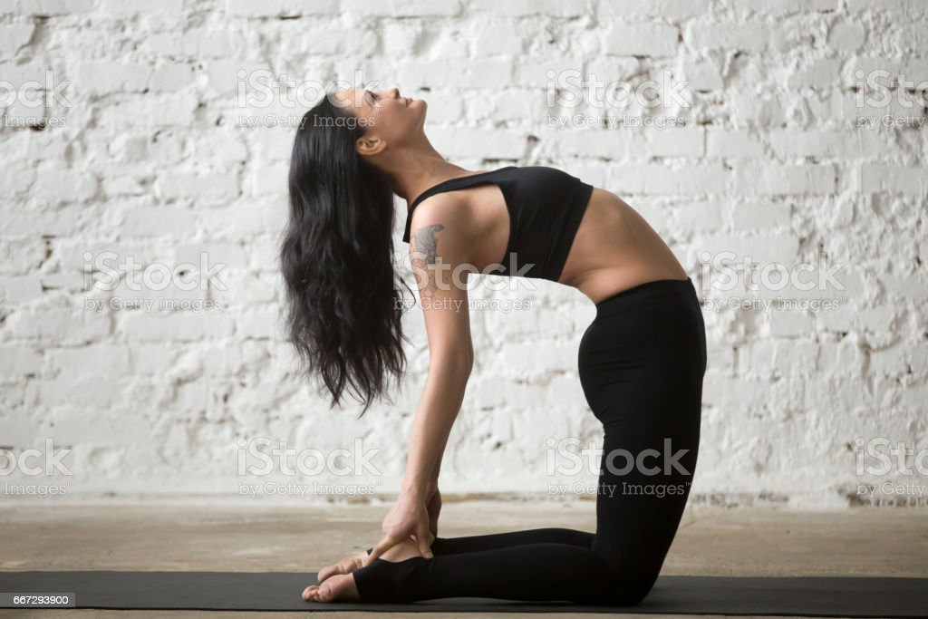 Young yogi attractive woman in Camel pose, white loft background stock photo