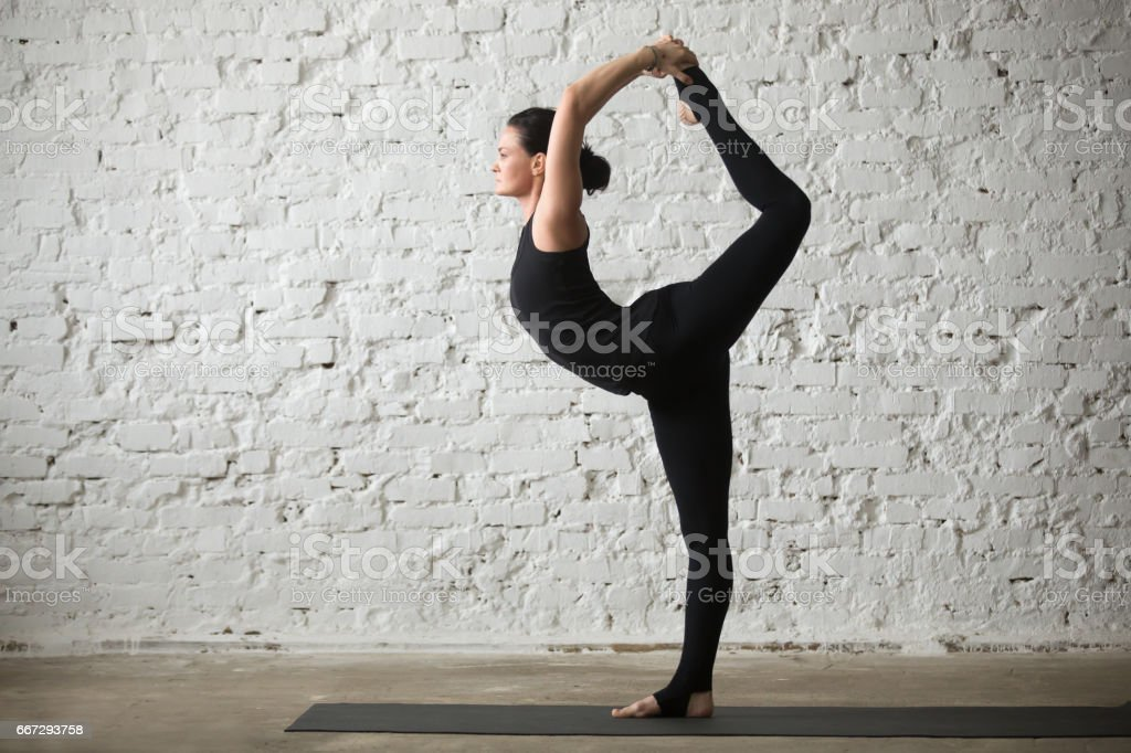 Young yogi attractive woman in Lord of the Dance pose stock photo