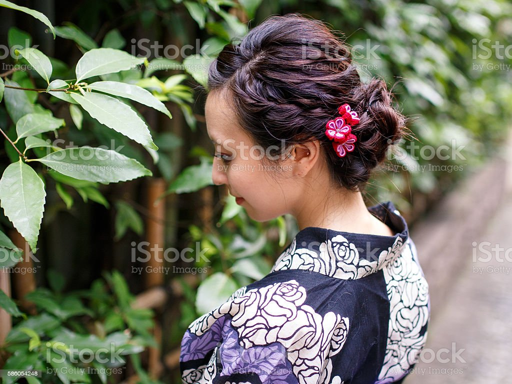 Young Yukata woman looking at green leaves stock photo
