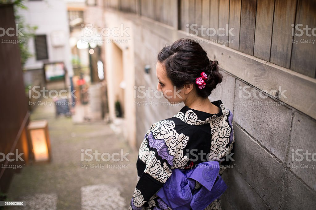 Young Yukata woman walking down narrow slope stock photo