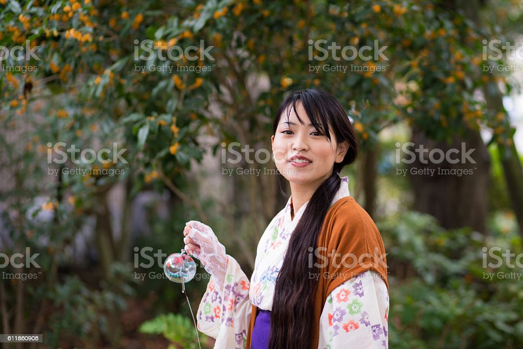 Young yukata woman walking in park with Japanese wind bell stock photo
