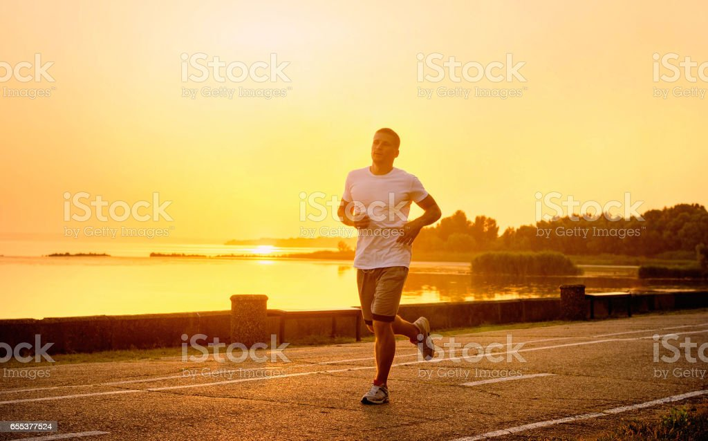 Youngathlete on the evening run of sunset. stock photo
