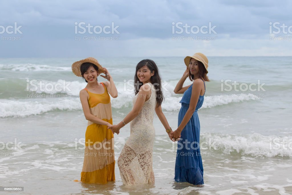 younger asian woman friend relaxing vacation time at sea beach happiness emotion stock photo