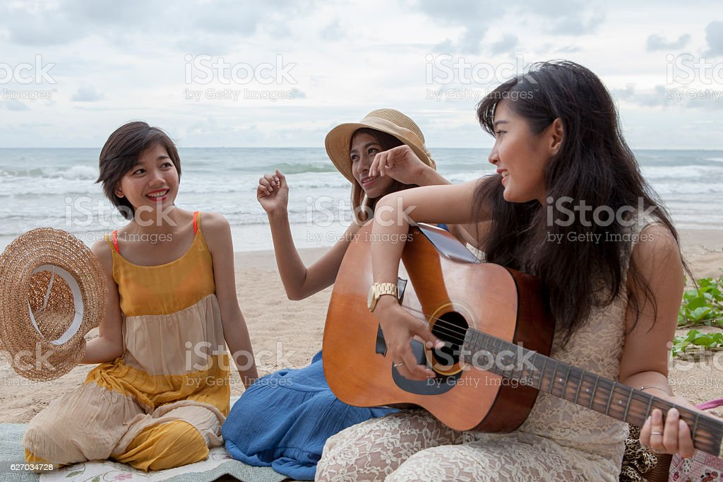 younger asian woman friend vacation relaxing playing guitar and stock photo
