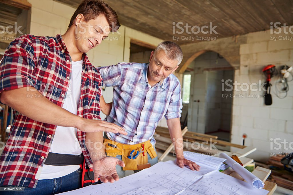 Younger of carpenters is demonstrating new idea stock photo