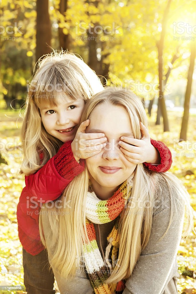 Younger sister standing behind older, covering her eyes royalty-free stock photo