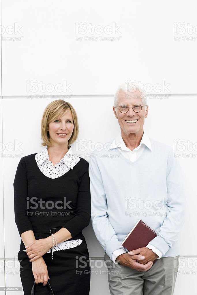 Younger woman and older man smiling stock photo