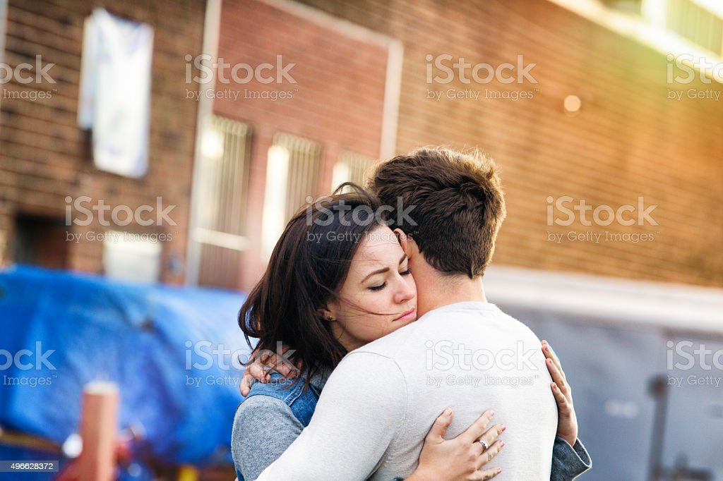 Youngle couple in love embracing alley urban sunset stock photo