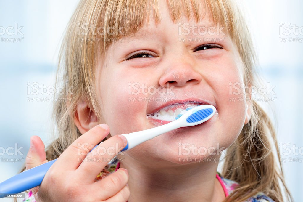 Youngster having fun brushing teeth. stock photo