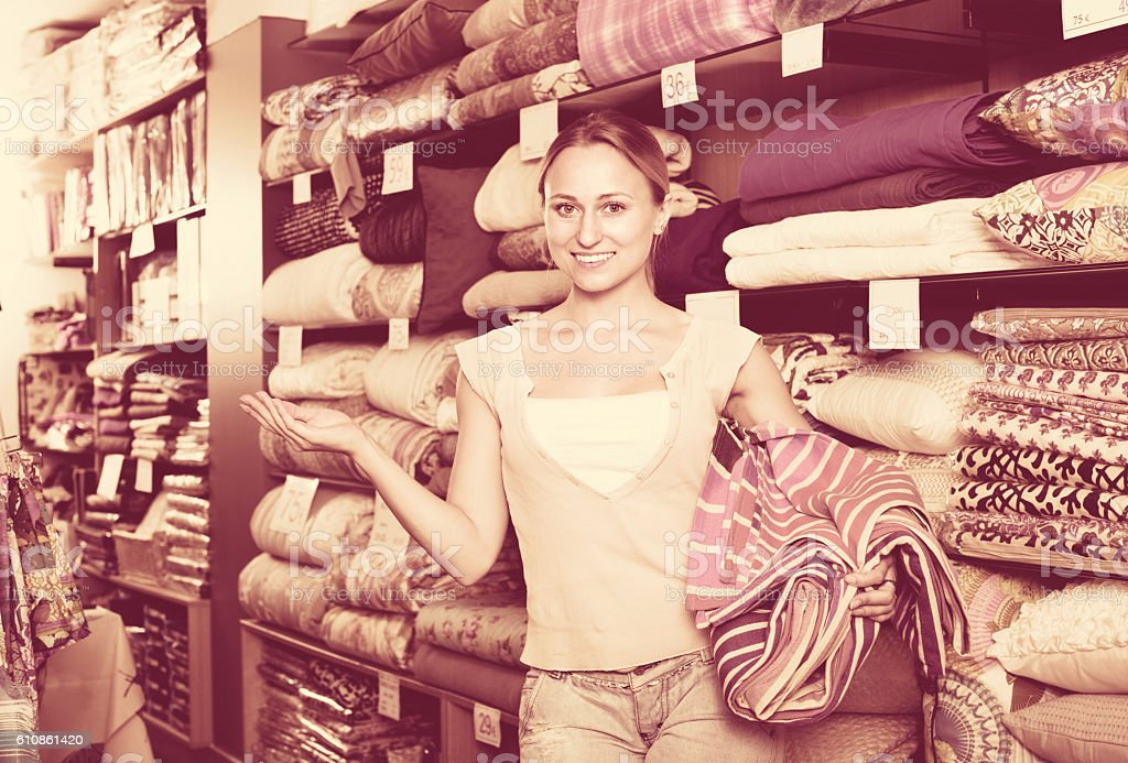 Youngwoman buying bed spread in  textile store stock photo