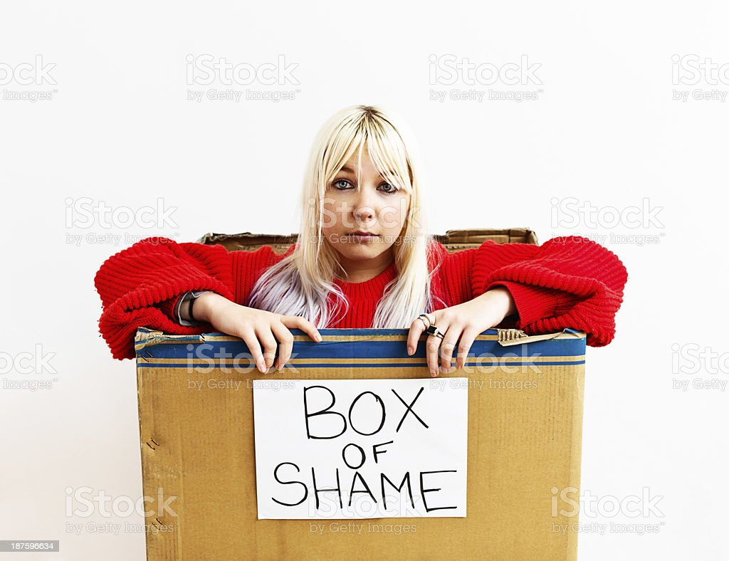 You're mean! Unhappy blonde confined to Box of Shame stock photo