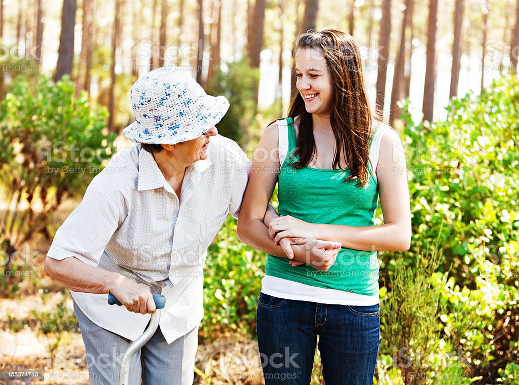 Youth and age: grandddaughter laughing with grandmother on forest walk stock photo