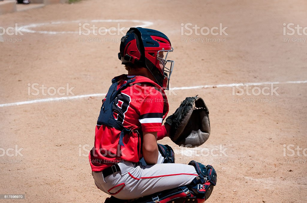 Youth baseball catcher behind home plate. stock photo