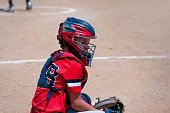 Youth baseball catcher looking at coach.