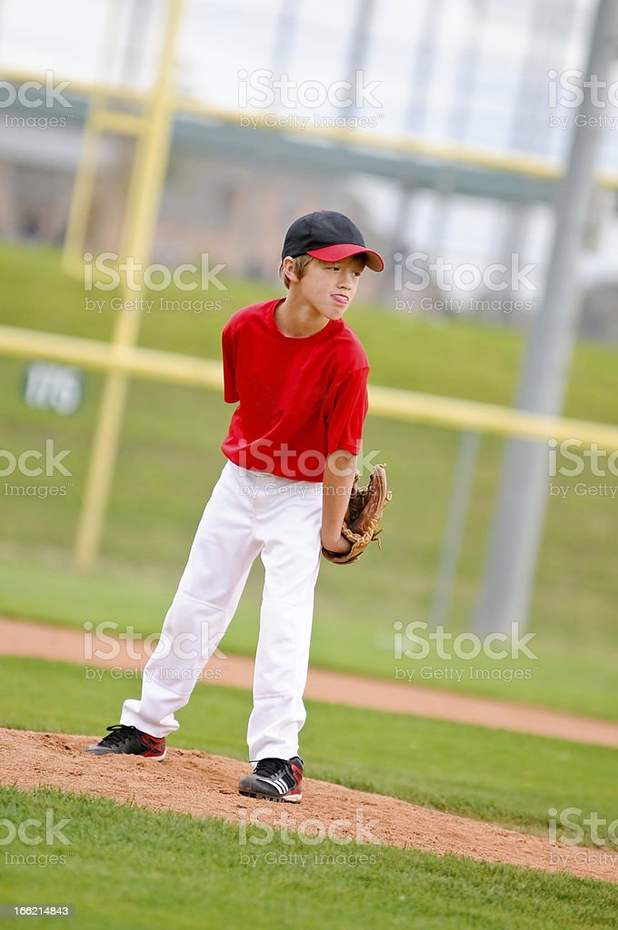 Youth baseball pitcher in red jersey stock photo