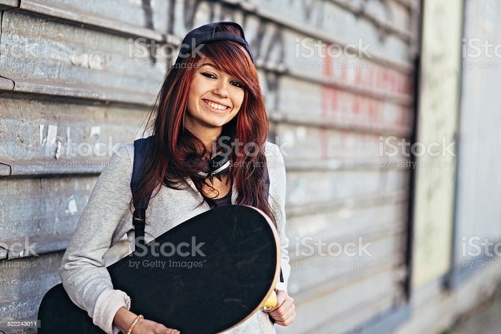 A teen girl holding a skateboard.