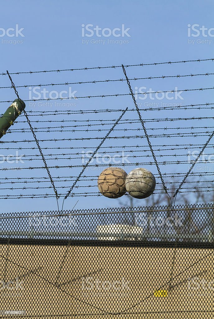 Youth detention centre fence with soccer balls on barbed wire stock photo